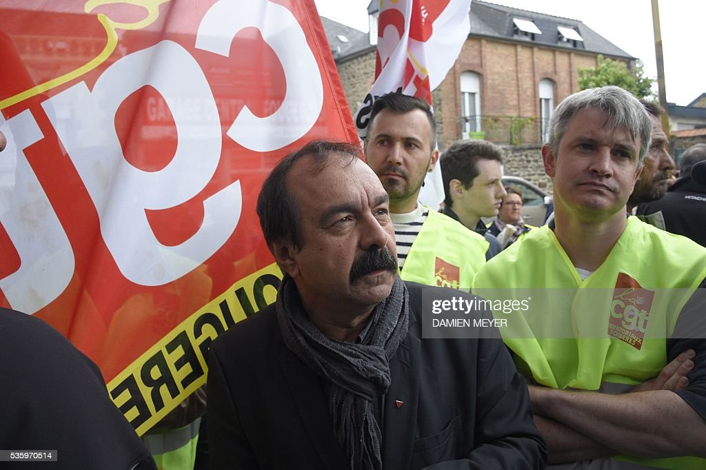 French secretary-general of the General Confederation of Labour (CGT) worker's union, Philippe Martinez stands next to CGT members holding flags in Fougeres, western France on May 31, 2016, as he declared that the CGT filed a lawsuit for defamation against the head of France's bosses' federation. French employers' association Medef Pierre Gattaz accused unions of behaving like 'terrorists', as the fresh industrial unrest was set to hit transport just days before fans begin arriving for the start of the football championships on June 10. / AFP / DAMIEN