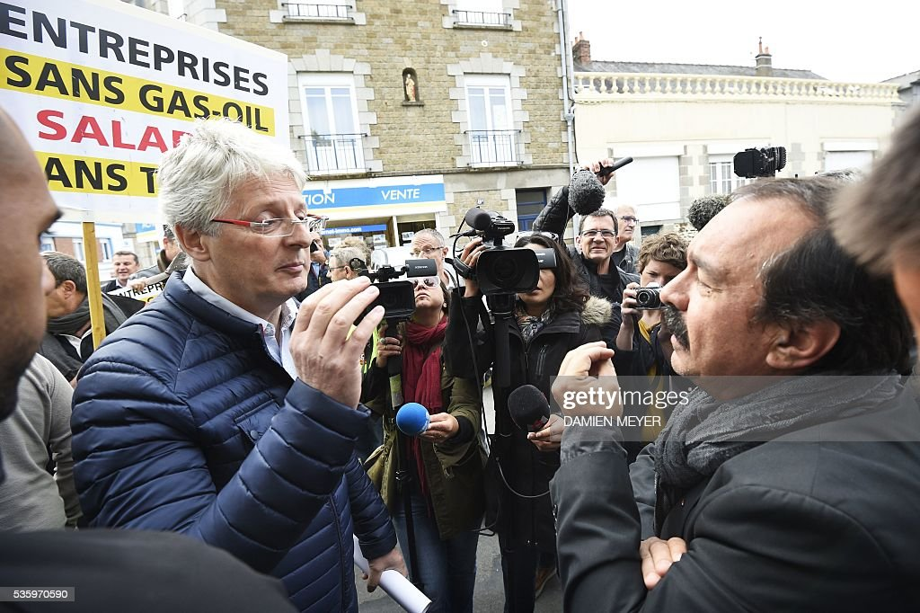 French secretary-general of the General Confederation of Labour (CGT) worker's union, Philippe Martinez speaks with an employer holding a counter demonstration in Fougeres, western France on May 31, 2016, as Martinez declared that the CGT filed a lawsuit for defamation against the head of France's bosses' federation. French employers' association Medef Pierre Gattaz accused unions of behaving like 'terrorists', as the fresh industrial unrest was set to hit transport just days before fans begin arriving for the start of the football championships on June 10. / AFP / DAMIEN