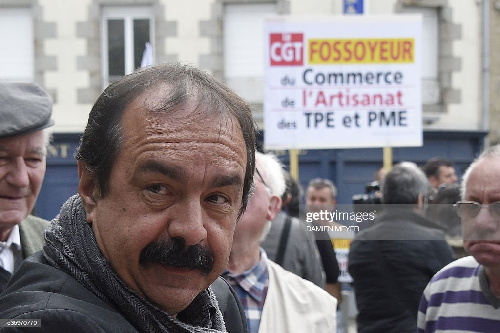 French secretary-general of the General Confederation of Labour (CGT) worker's union, Philippe Martinez stands next to a banner of a counter demonstration reading 'CGT gravedigger of Trade and business' in Fougeres, western France on May 31, 2016, where Martinez declared that the CGT filed a lawsuit for defamation against the head of France's bosses' federation. French employers' association Medef Pierre Gattaz accused unions of behaving like 'terrorists', as the fresh industrial unrest was set to hit transport just days before fans begin arriving for the start of the football championships on June 10. / AFP / DAMIEN