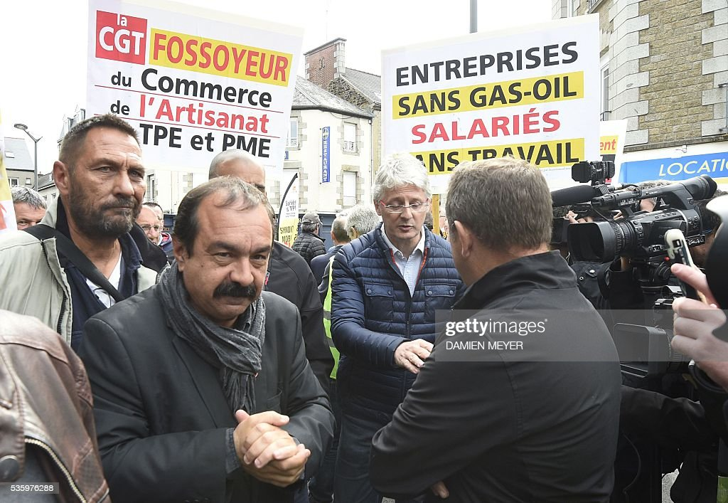 French secretary-general of the General Confederation of Labour (CGT) worker's union Philippe Martinez (L) walks next to banners of a counter demonstration hold by employers reading 'CGT gravedigger of Trade and business' and 'companies without oil, employees and work' in Fougeres, western France on May 31, 2016, where Martinez declared that the CGT filed a lawsuit for defamation against the head of France's bosses' federation. French employers' association Medef Pierre Gattaz accused unions of behaving like 'terrorists', as the fresh industrial unrest was set to hit transport just days before fans begin arriving for the start of the football championships on June 10. / AFP / DAMIEN