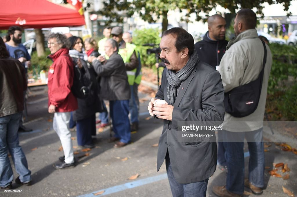 French secretary-general of the General Confederation of Labour (CGT) worker's union Philippe Martinez surrounded by CGT members holds a drink in Fougeres, western France on May 31, 2016, as he declared that the CGT filed a lawsuit for defamation against the head of France's bosses' federation. French employers' association Medef Pierre Gattaz accused unions of behaving like 'terrorists', as the fresh industrial unrest was set to hit transport just days before fans begin arriving for the start of the football championships on June 10. / AFP / DAMIEN