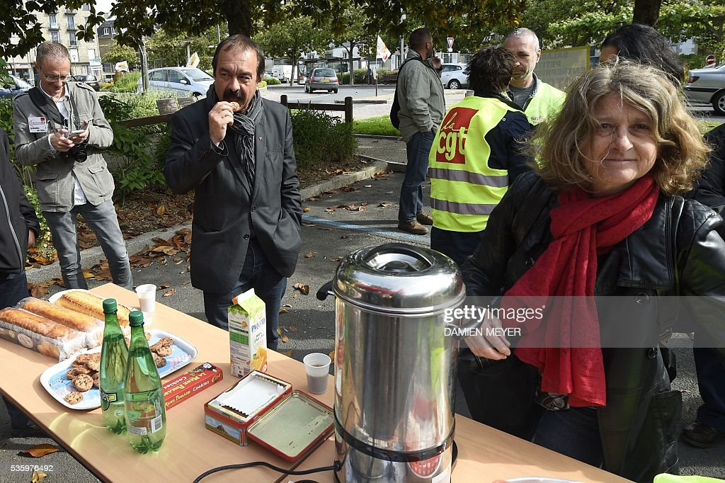 French secretary-general of the General Confederation of Labour (CGT) worker's union Philippe Martinez surrounded by CGT members eats in Fougeres, western France on May 31, 2016, as he declared that the CGT filed a lawsuit for defamation against the head of France's bosses' federation. French employers' association Medef Pierre Gattaz accused unions of behaving like 'terrorists', as the fresh industrial unrest was set to hit transport just days before fans begin arriving for the start of the football championships on June 10. / AFP / DAMIEN
