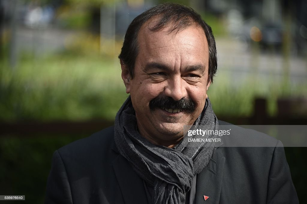 French secretary-general of the General Confederation of Labour (CGT) worker's union Philippe Martinez smiles in Fougeres, western France on May 31, 2016, as he declared that the CGT filed a lawsuit for defamation against the head of France's bosses' federation. French employers' association Medef Pierre Gattaz accused unions of behaving like 'terrorists', as the fresh industrial unrest was set to hit transport just days before fans begin arriving for the start of the football championships on June 10. / AFP / DAMIEN