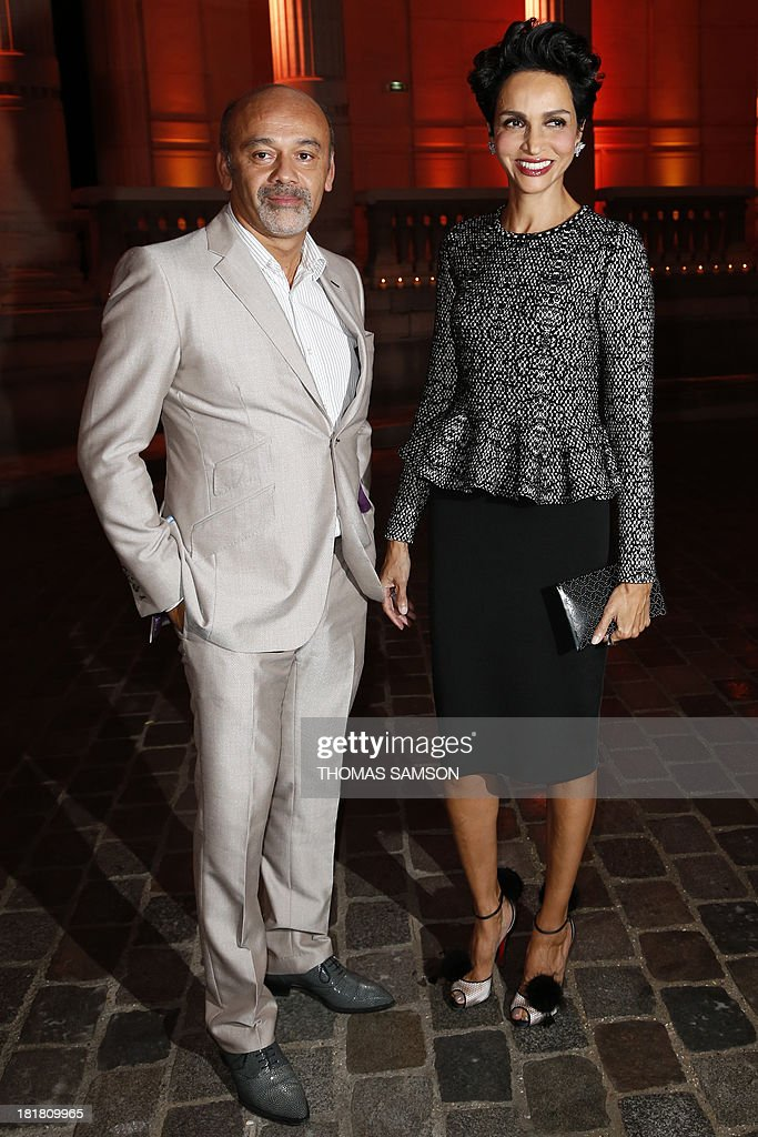 French shoe designer Christian Louboutin (L) and French actress and former model Farida Khelfa pose at the launching of the exhibition 'Alaia' dedicated to French fashion designer Azzedine Alaia at the Galliera Palace in Paris on September 25, 2013. AFP PHOTO THOMAS SAMSON