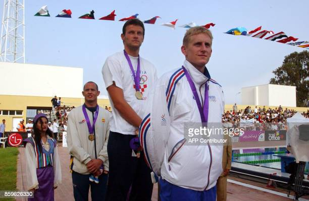French Simon Dufour Croatian Marko Strahijo and Spanish Jorge Sanchez pose 04 September 2001 on the podium of the men's 200m backstroke event of the...