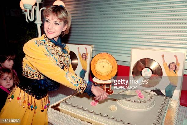 French singer actress and TV host Dorothée cuts a cake to celebrate her Golden record on December 17 1988 at the Zenith Theater in Paris AFP...