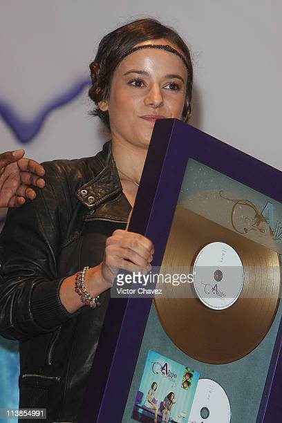 French singer Alizee handling a gold disc for more than 50000 sales of her album 'Psichédélices' at Plaza Inbursa on June 26 2008 in Mexico Mexico...
