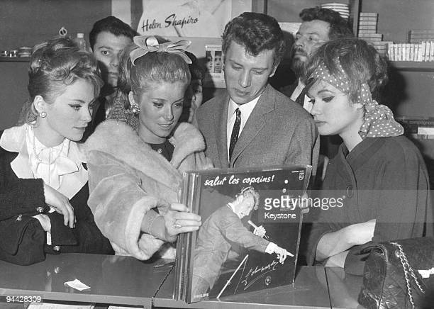 French singer and actor Johnny Hallyday and actress Catherine Deneuve find a copy of Hallyday's record 'Salut les Copains' at a record shop in Paris...