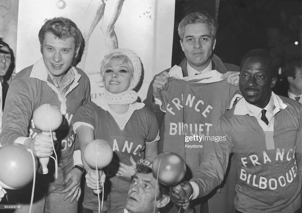 French singer and actor Johnny Hallyday attends a bilboquet championship at a Paris club, 24th November 1965. From left to right, Hallyday, Maria Vincent, Sydney Chaplin and bilboquet champion Le Mecque.