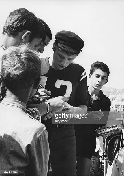French singer and actor Johnny Hallyday signs autographs for a group of fans whilst holidaying on the Cote d'Azur 12th August 1965