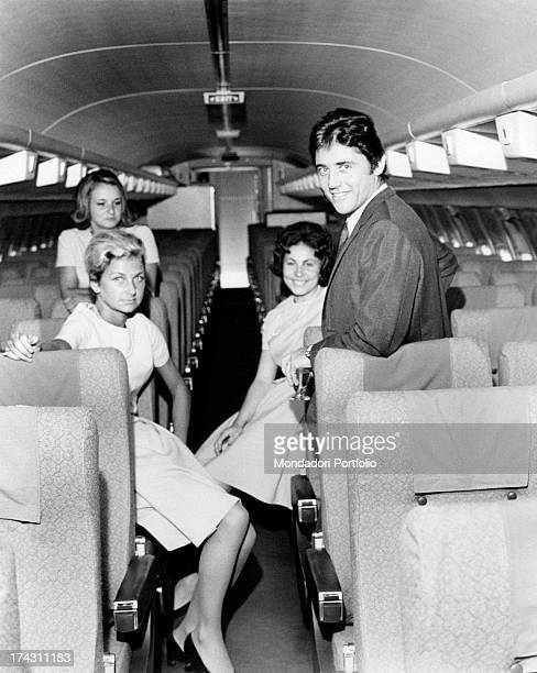 French singer and actor Sacha Distel smiling in company of some hostesses on an aeroplane Paris July 1968