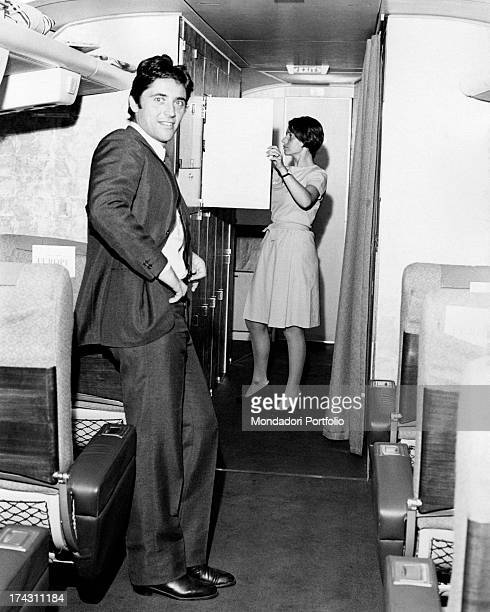 French singer and actor Sacha Distel smiling in the aisle of an aeroplane while a hostess checks the content of a locker Paris July 1968