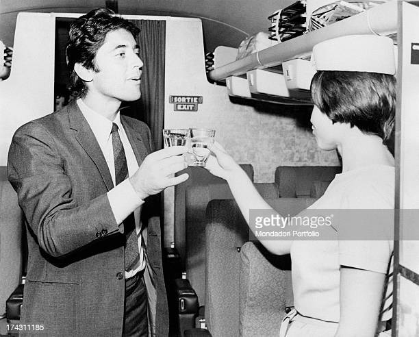 French singer and actor Sacha Distel toasting with a hostess in the aisle of an aeroplane Paris July 1968