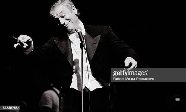 French singer and actor Yves Montand performing on stage at the Olympia