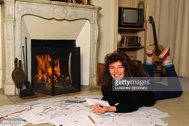 French singer and actress Elsa Lunghini reading fan letters at home