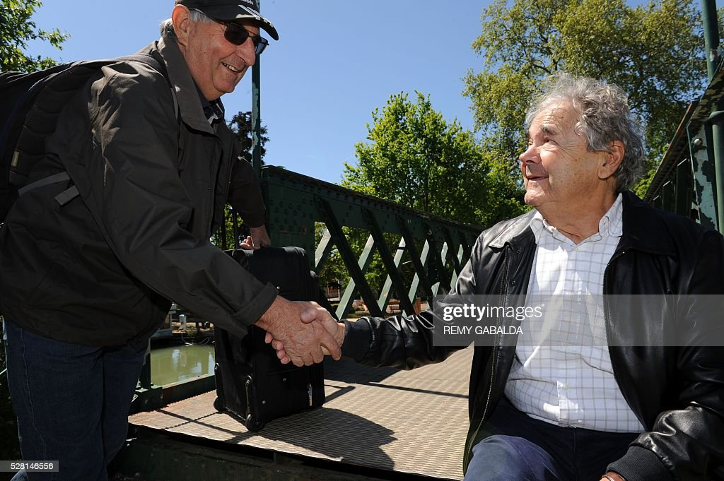 French singer and composer Pierre Perret shakes the hand of a man along the Canal du Midi during the 'Alors Chante' music festival, on May 4, 2016, in his city of birth Castelsarrasin in the south west of France. GABALDA