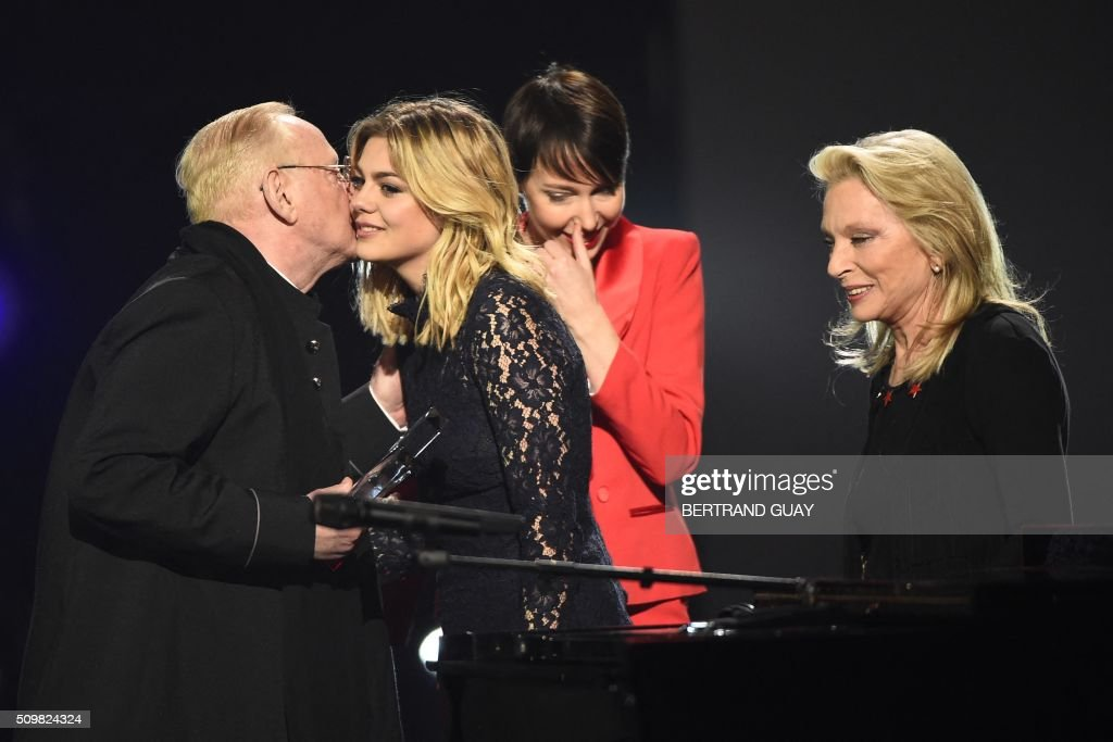 French singer and composer William Sheller (L) embraces French singer Louane after he received a special honour, as French singers Jeanne Cherhal (2nd R) and Veronique Sanson (R) look on, during the 31st Victoires de la Musique, the annual French music awards ceremony, on February 12, 2016 at the Zenith concert hall in Paris. AFP PHOTO / BERTRAND GUAY / AFP / BERTRAND GUAY