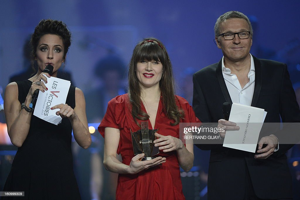 French singer Camille (C) holds her trophy for the best original song of the year award, surrounded by French TV hosts and Masters of Ceremony Virginie Guilhaume and Laurent Ruquier during the 28th Victoires de la Musique, the annual French music awards ceremony, on February 8, 2013 at the Zenith concert hall in Paris.
