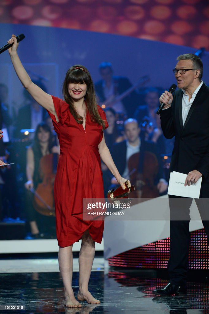 French singer Camille (L) raises her arm as she holds her trophy for the best original song of the year award during the 28th Victoires de la Musique, the annual French music awards ceremony, on February 8, 2013 at the Zenith concert hall in Paris.