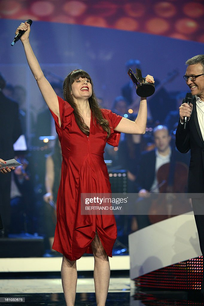 French singer Camille (L) raises her arm as she holds her trophy for the best original song of the year award during the 28th Victoires de la Musique, the annual French music awards ceremony, on February 8, 2013 at the Zenith concert hall in Paris. AFP PHOTO / BERTRAND GUAY