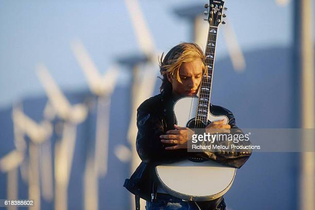 French singer David Hallyday holds his guitar as he stands near a line of windmills in Palm Springs David is the son of the legendary French musician...