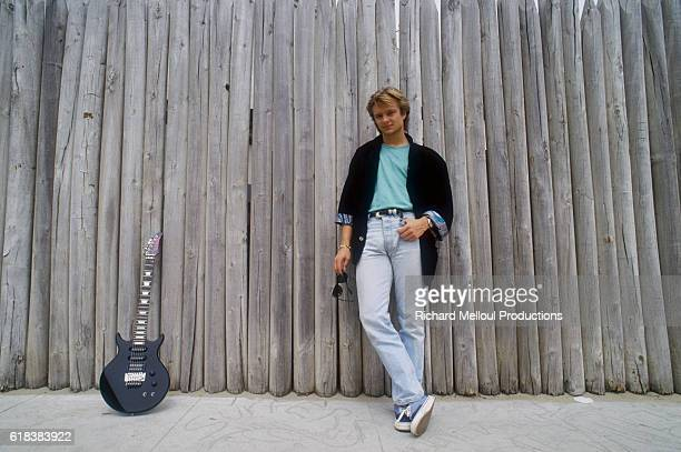 French singer David Hallyday leans against a wooden fence near his electric guitar