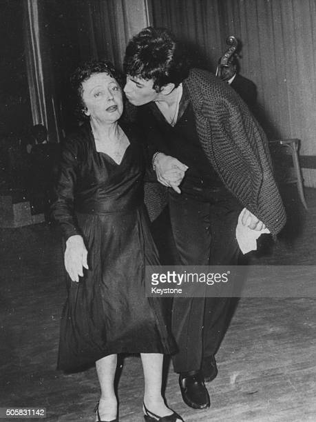 French singer Edith Piaf being kissed on the cheek by her husband Theo Sarapo at the Palais des Festivals in Cannes following the announcement of...