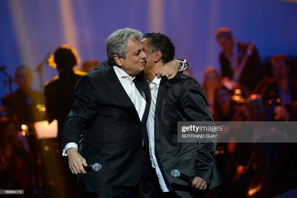 French singer Enrico Macias (L) hugs Algerian singer Khaled after performing on stage following his honorary award for his 50-year career during the 28th Victoires de la Musique, the annual French music awards ceremony, on February 8, 2013 at the Zenith concert hall in Paris. AFP PHOTO / BERTRAND GUAY
