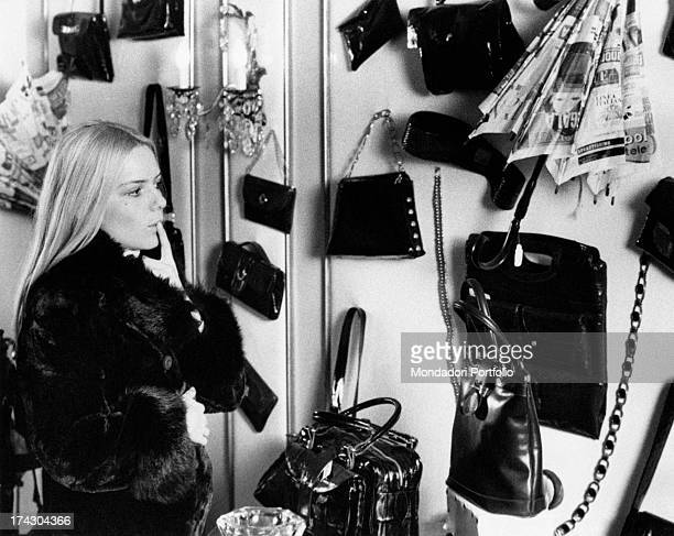 French singer France Gall looking at the items on sale in a bag shop 1970