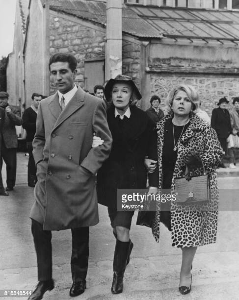 French singer Gilbert Bécaud escorts actress Marlene Dietrich to the funeral of artist and writer Jean Cocteau at La Foret France 17th October 1963