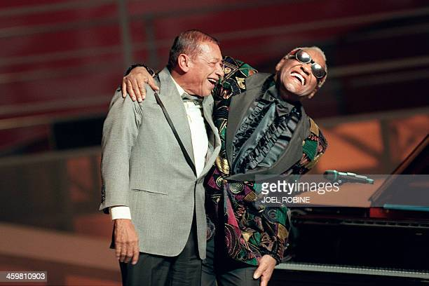 French singer Henri Salvador and US jazz musician Ray Charles acknowledge applause after performing during the 11th 'Victoires de la Musique'...