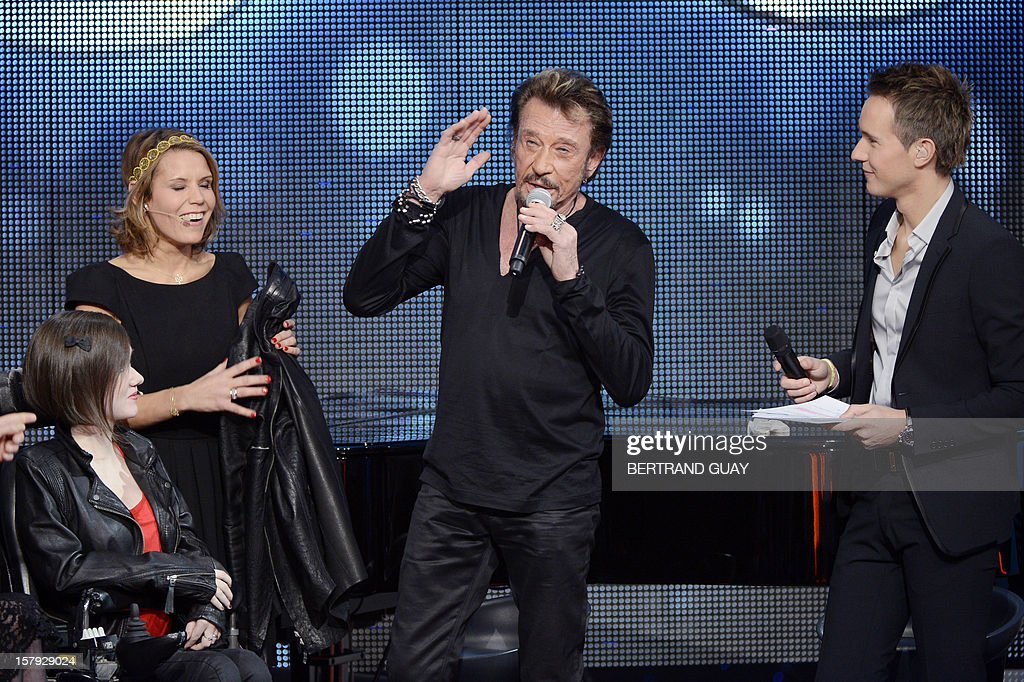 French singer Johnny Hallyday (C) and French TV host Cyril Feraud (R) attend the 26th Telethon, France's biggest annual fund-raising event during 30 hours of live television transmission, on December 7, 2012 in Saint-Denis, north of Paris. The event, aiming at collecting funds for research on genetic diseases such as myopathy, a neuromuscular disease, will take place on December 7 and 8, 2012. AFP PHOTO / BERTRAND GUAY