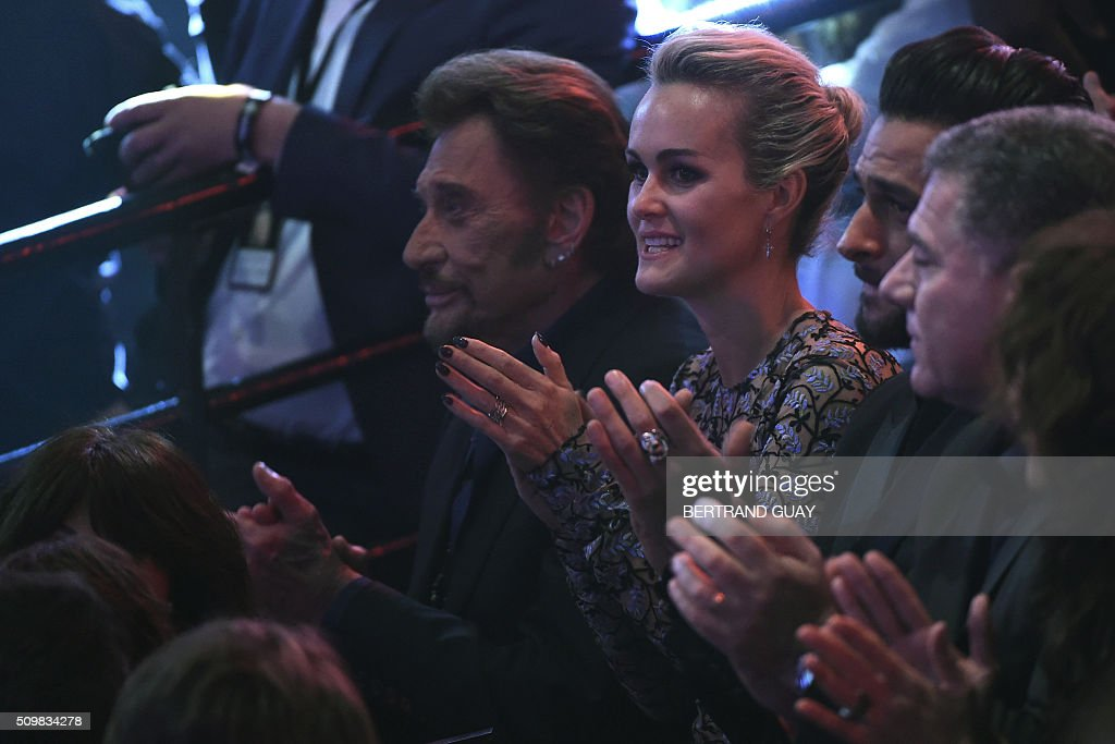 French singer Johnny Hallyday (L) and his wife Laeticia (C) attend the 31st Victoires de la Musique, the annual French music awards ceremony, on February 12, 2016 at the Zenith concert hall in Paris. AFP PHOTO / BERTRAND GUAY / AFP / BERTRAND GUAY