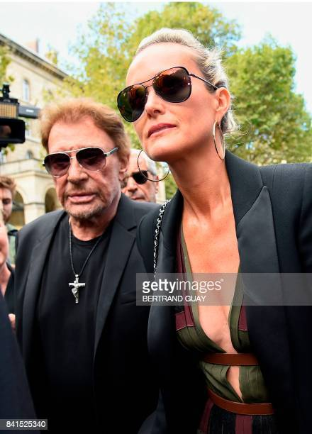 French singer Johnny Hallyday and his wife Laeticia Hallyday arrive at the SaintSulpice church to attend the funeral of late actress Mireille Darc on...