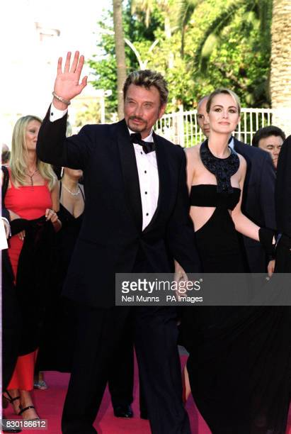 French singer Johnny Hallyday and his wife model Laetitia arrive for the premiere of the film 'An Ideal Husband' in Cannes France during the 52nd...