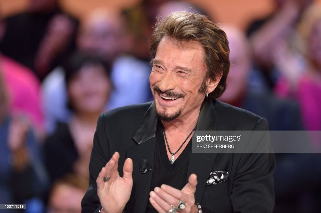 French singer Johnny Hallyday applauds as he takes part in the TV show 'Le grand journal' on a set of French TV Canal+, on November 19, 2012 in Paris, to present his new album entitled, 'The wait'.