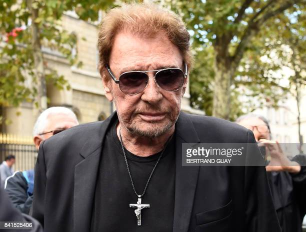 French singer Johnny Hallyday arrives at the SaintSulpice church to attend the funeral of late actress Mireille Darc on September 1 2017 in Paris...
