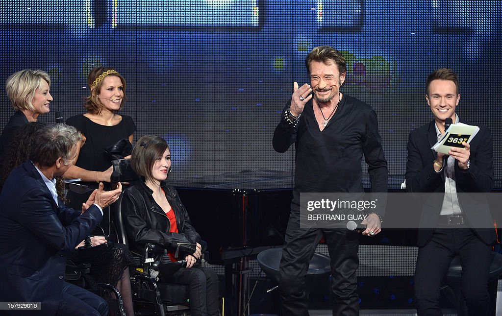 French singer Johnny Hallyday (C), French TV hosts Sophie Davant (L) and Cyril Feraud (R) attend the 26th Telethon, France's biggest annual fund-raising event during 30 hours of live television transmission, on December 7, 2012 in Saint-Denis, north of Paris. The event, aiming at collecting funds for research on genetic diseases such as myopathy, a neuromuscular disease, will take place on December 7 and 8, 2012.