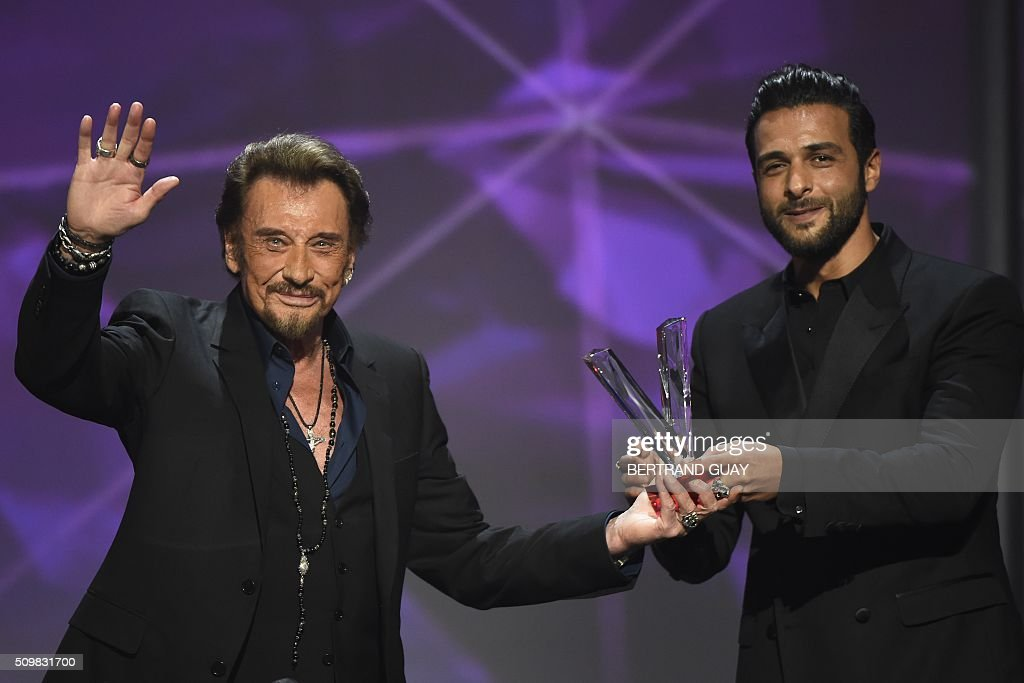 French singer Johnny Hallyday (L) gestures as he receives the best album award composed by Maxim Nucci alias Yodelice (R), during the 31st Victoires de la Musique, the annual French music awards ceremony, on February 12, 2016 at the Zenith concert hall in Paris. AFP PHOTO / BERTRAND GUAY / AFP / BERTRAND GUAY