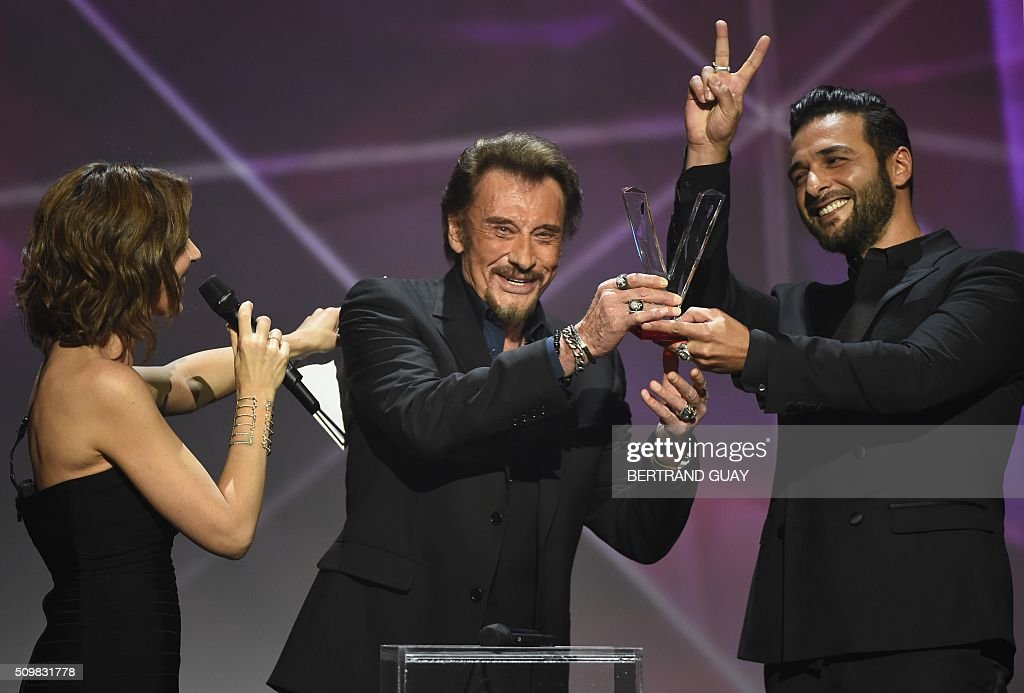 French singer Johnny Hallyday (C) gestures as he receives the best album award composed by Maxim Nucci alias Yodelice (R), during the 31st Victoires de la Musique, the annual French music awards ceremony, on February 12, 2016 at the Zenith concert hall in Paris. AFP PHOTO / BERTRAND GUAY / AFP / BERTRAND GUAY