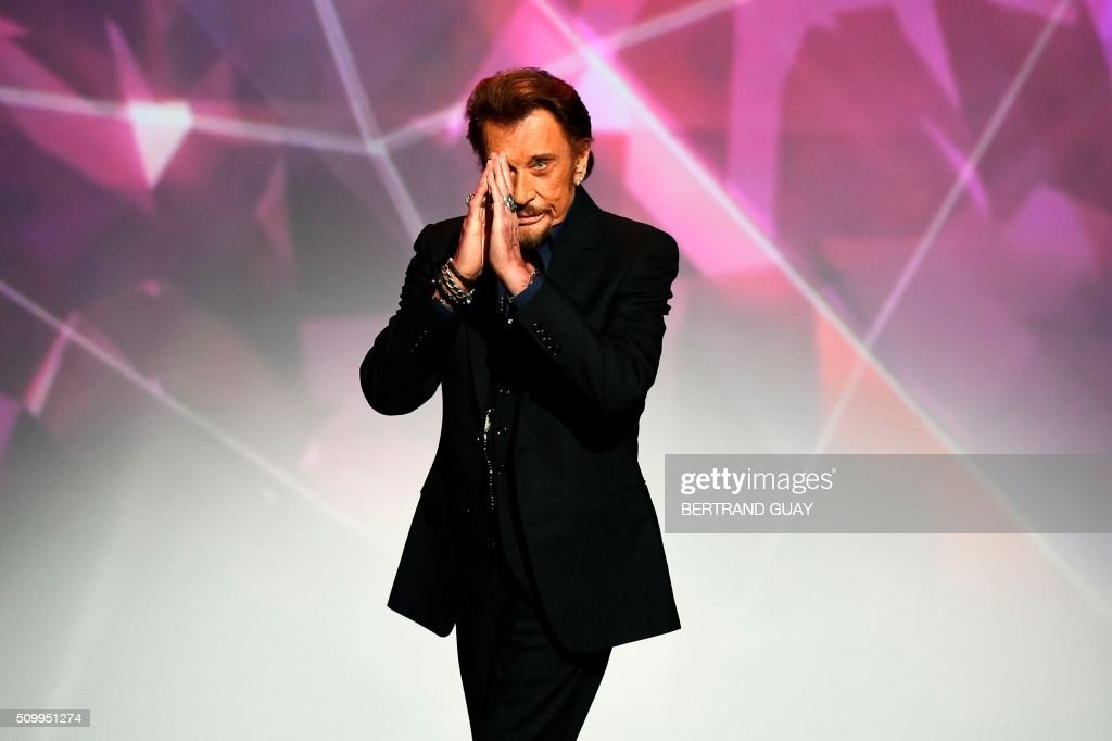 French singer Johnny Hallyday gestures as he receives the best album award on stage during the 31st Victoires de la Musique, the annual French music awards ceremony, on February 12, 2016 at the Zenith concert hall in Paris. / AFP / BERTRAND GUAY