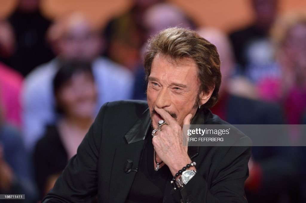 French singer Johnny Hallyday gestures as he takes part in the TV show 'Le grand journal' on a set of French TV Canal+, on November 19, 2012 in Paris, to present his new album entitled, 'The wait'.