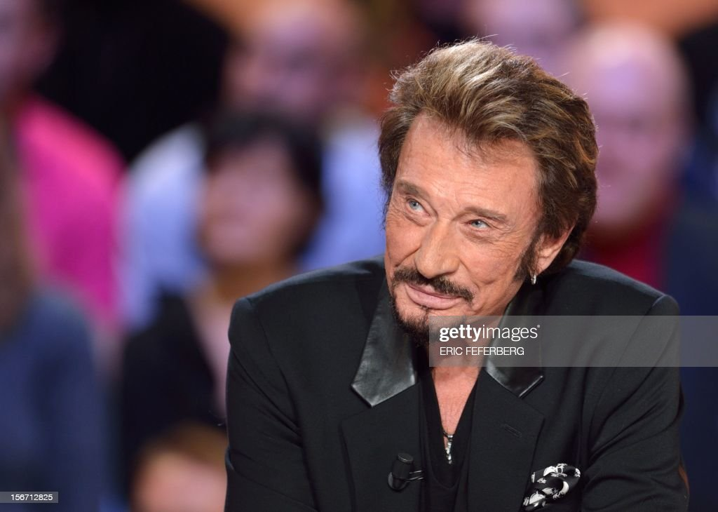 French singer Johnny Hallyday listens as he takes part in the TV show 'Le grand journal' on a set of French TV Canal+, on November 19, 2012 in Paris, to present his new album entitled, 'The wait'.