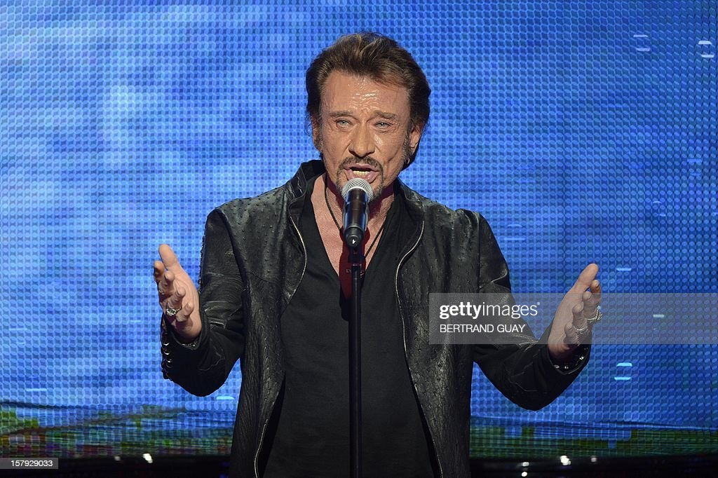 French singer Johnny Hallyday performs during the 26th Telethon, France's biggest annual fund-raising event during 30 hours of live television transmission, on December 7, 2012 in Saint-Denis, north of Paris. The event, aiming at collecting funds for research on genetic diseases such as myopathy, a neuromuscular disease, will take place on December 7 and 8, 2012. AFP PHOTO / BERTRAND GUAY