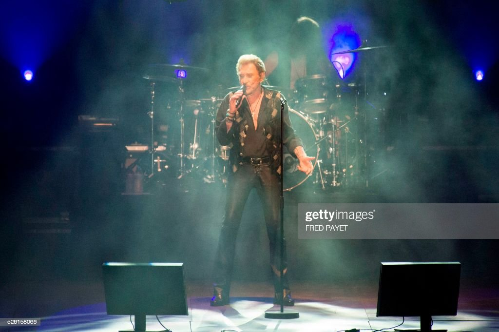 French singer Johnny Hallyday sings at the Numa-Dely stadium in Noumea on April 29, 2016 during his concert. / AFP / Fred Payet