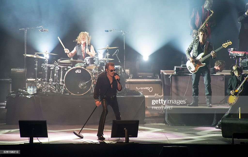 French singer Johnny Hallyday (C) performs on stage during his concert at the Numa-Dely stadium in Noumea on April 29, 2016. / AFP / Fred Payet