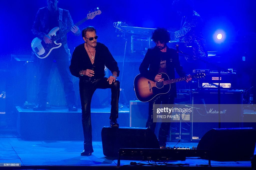 French singer Johnny Hallyday (L) performs on stage during his concert at the Numa-Dely stadium in Noumea on April 29, 2016. / AFP / Fred Payet