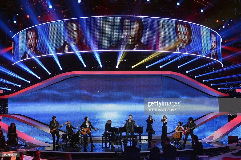 French singer Johnny Hallyday (C) performs on stage during the 26th Telethon, France's biggest annual fund-raising event broadcast on television during 30 hours, on December 7, 2012 in Saint-Denis, north of Paris. The event, aiming at collecting funds for research on genetic diseases such as myopathy, a neuromuscular disease, will run until December 8, 2012.