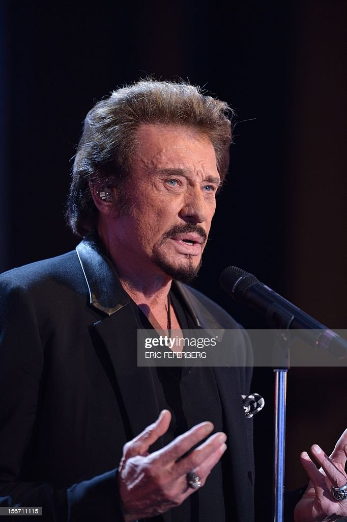 French singer Johnny Hallyday sings a song of his new album entitled, 'The wait', as he takes part in the TV show 'Le grand journal' on a set of French TV Canal+, on November 19, 2012 in Paris.