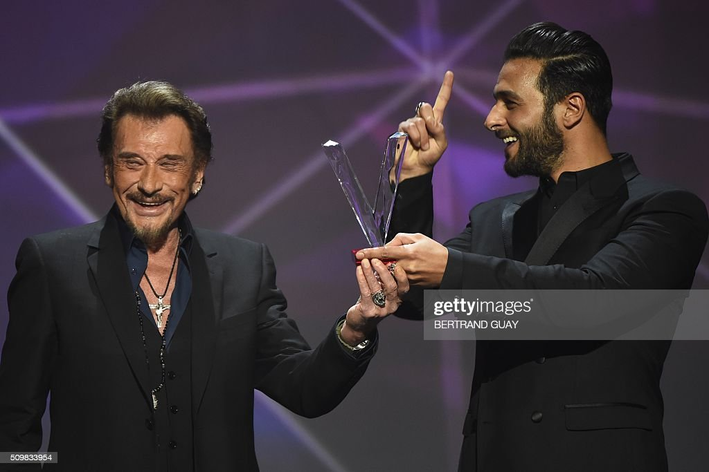 French singer Johnny Hallyday (L) smiles as he receives the best album award composed by Maxim Nucci alias Yodelice (R), during the 31st Victoires de la Musique, the annual French music awards ceremony, on February 12, 2016 at the Zenith concert hall in Paris. AFP PHOTO / BERTRAND GUAY / AFP / BERTRAND GUAY